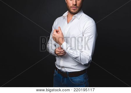 Untroubled well-dressed man standing and fixing the button on handcuff. Isolated on black background. Copy space in left side
