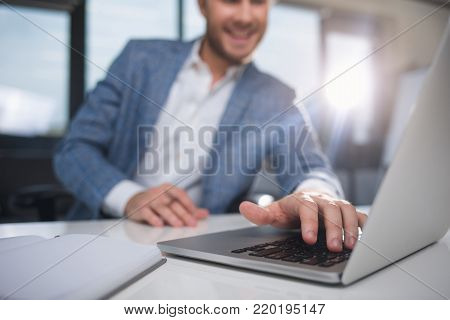 Smiling businessman sitting in the office and typing on a computer. Focus on device