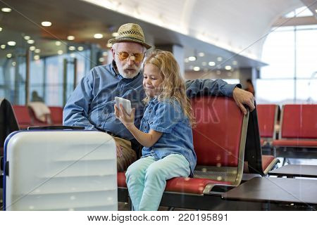 Look at this. Optimistic granddaughter is sitting on red bench at airport lounge with her grandfather while showing him screen of mobile phone. They are expressing interest while looking at display