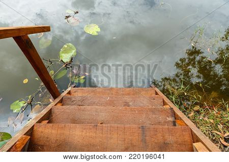 wooden ladder for swimming descending to lake