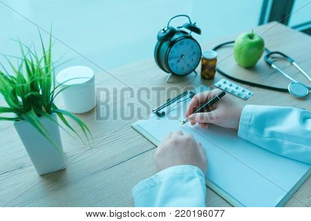 General practitioner writing notes during medical exam, prescription medicine and healthcare, blue toned image