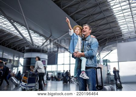 Feeling wonder. Low angle of curious pretty daughter is pointing out to something interesting at airport while being on hands of her mature father. They are expressing amaze. Copy space in left side