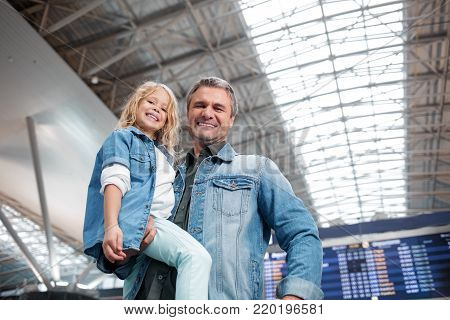 Feeling excited. Low angle portrait of optimistic mature father is holding his cute daughter while standing at modern airport and laughing. They are looking at camera with joy