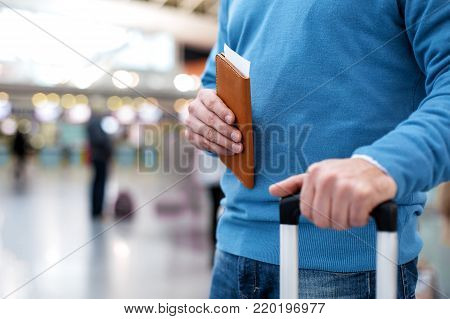 Close-up of male hands is keeping flight tickets while standing at airport and holding handle of suitcase. Copy space in the left side. People in background
