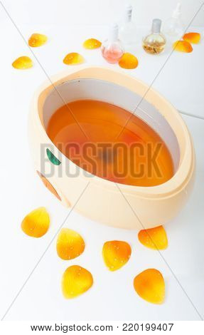Orange parrafin wax in bowl and petals. Manicure and skincare in beauty spa salon.