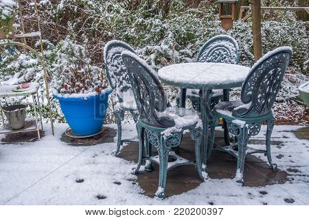 Snow covers a table on a back porch in the Pacific Northwest.