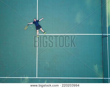 Tennis player tired after game and lay on tennis court above view