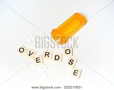 Overdose spelled with haphazard tile letters with small white pills and an open prescription bottle. Photographed from above on a white background. Image has copy space.