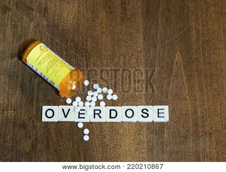 Overdose spelled with tile letters in a row with small white pills and an open prescription bottle. Photographed from above on a wooden table. Image has copy space.