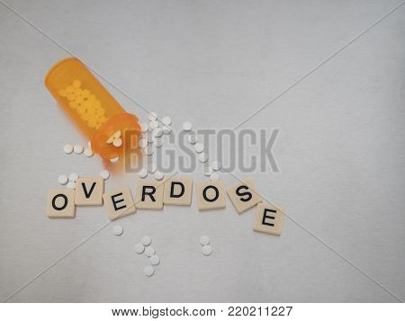 Overdose spelled with tile letters placed in a row with an syringe filled with clear liquid and an empty Fentanyl vial. Photographed from above on a stainless steel background. Image has copy space.