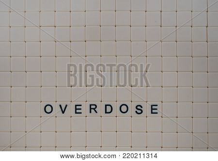 Tan tiles with black capital letters spelling Overdose set in a background of small tan tiles.  Image has copy space. Photographed from above.