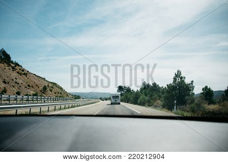 Asphalt highway in mountains with cars on the road in sunny morning