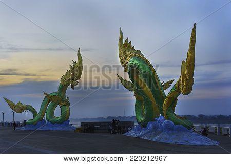 Nong Khai ,Thailand - December 25 , 2017 : People relaxing around Naga statue , one of Landmarks at Sadet pier along Mekong river