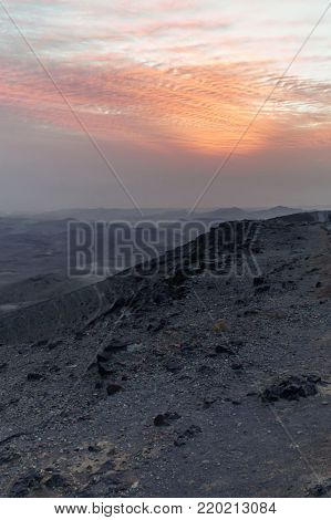 Vertical photo magic sunrise dawn over holy land judean desert in Israel. Landscape with beautiful red sun and blue clouds. Road to infinite violet land. Nobody on photo.