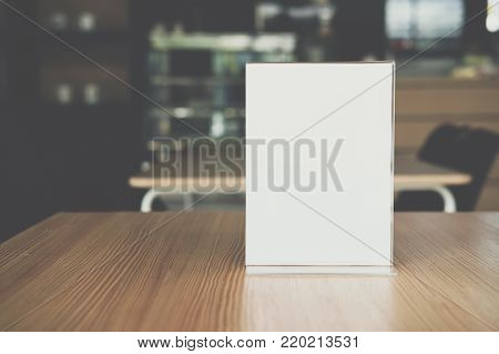 White Label In Cafe. Display Stand For Acrylic Tent Card In Coffee Shop. Mockup Menu Frame On Table