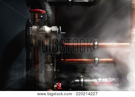 Smoke and steam in a boiler room. Copper pipes and valves on a wet boiler.Phrase on boiler