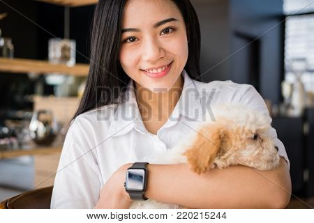 young woman holding adorable dog at cafe restaurant. female teenager with pet at coffee shop. people, animal, lifestyle concept