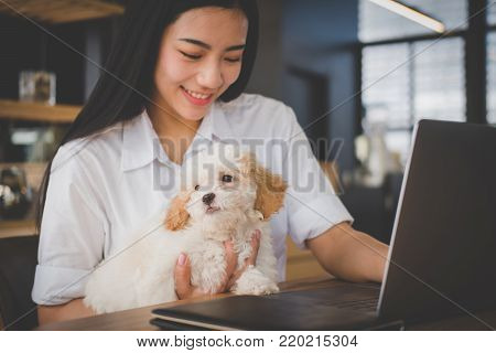 Woman Holding Adorable Dog At Cafe Restaurant. Female Teenager Student With Pet & Computer At Coffee