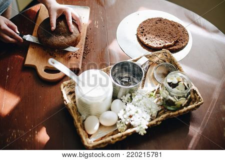 woman hands makin cake close up on wooden table