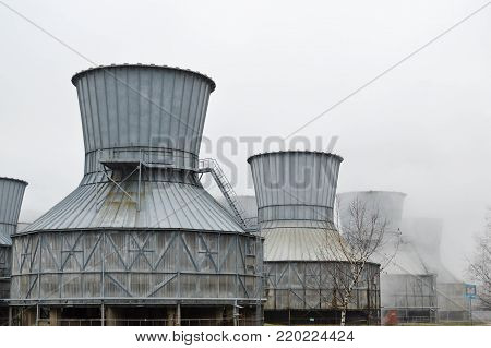 Large cooling towers in water and fog at an oil refinery, petrochemical, chemical plant. Heat-exchange equipment.
