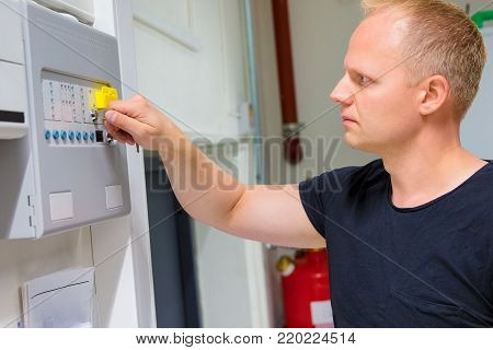 Confident mid adult male IT engineer opening fire panel in server room