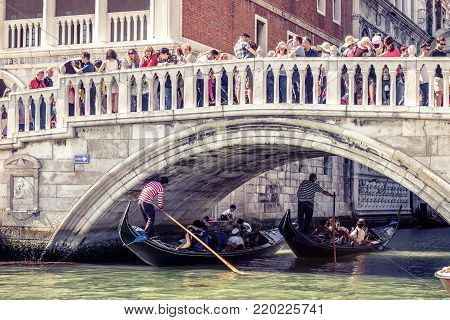 Venice, Italy - May 21, 2017: Gondolas with tourists floats near the famous Doge`s Palace (Palazzo Ducale) on the St Mark`s Square. Doge`s Palace is one of the main tourist attractions of Venice.