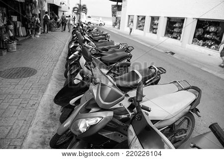 colorful scooters or motorcycles for sale or hire standing in row with wheels and lights on street road outdoor in Cozumel, Mexico, hiring transportation, traveling
