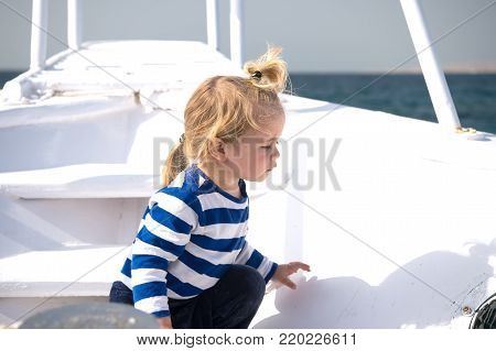 Boy in sailor shirt on blue sea. Summer vacation concept. Travel destination, cruise, travelling. Adventure, discovery, wanderlust. Child with blond hair on yacht on sunny day. poster