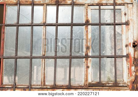 Window of old abandoned prison building with metal bars and dirty glass close up