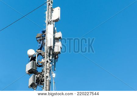 Technician electrician worker climbed up on telecommunication antenna metal tower to fix disconnection for television signal