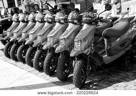 Key West, Florida - January 09, 2016: scooters or motorcycles for sale or hire standing in row with wheels and lights sunny day outdoor, hiring transportation, traveling