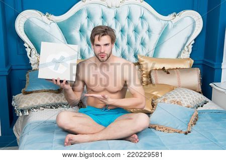 Man In Underwear Point At Boxes On Bed In Bedroom