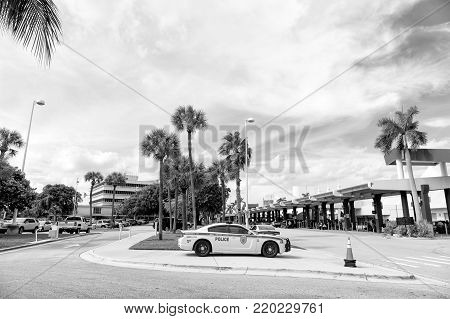 MIAMI , USA- DECEMBER 2, 2013: police car on Miami street. 911 auto on sidewalk road near parking zone with traffic cone, people, green palm trees sunny summer outdoor on blue sky background