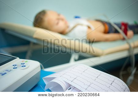 Electrocardiogram, cardiac cardiograph and conduct research in pediatrics, a girl doing an electrocardiogram