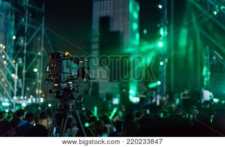 Video camera starting record concert live streaming show in the tv on the front stage lights with crowd fan in music festival
