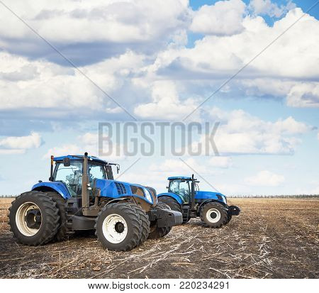 Tractors working on the farm, a modern agricultural transport, cultivation of fertile land, tractor on cloudy sky background, agricultural machine