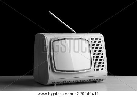 Old small TV set on a black background