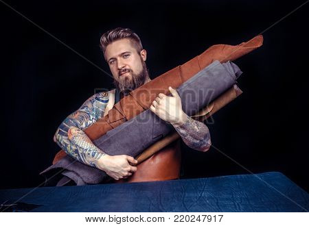 Leather craft or leather working. Selected pieces of beautifully colored or tanned leather in leather craftman's tattooed hands.