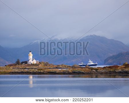 Lighthouse on Isle of Ornsay, the southern side of Isle of Skye, Scotland. Trade ship at rocky island, mountains in background