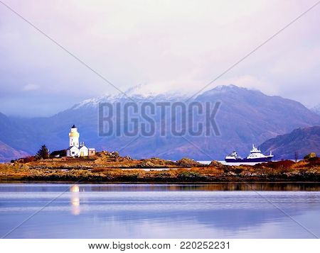 Famous Isle Ornsay with  Lighthouse tower, Isle of Skye, Scotland, UK. Snowy mountains in background.