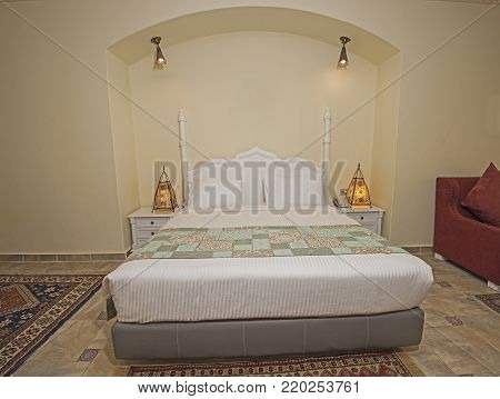 Double bed in suite of a luxury hotel room with bedside lamps