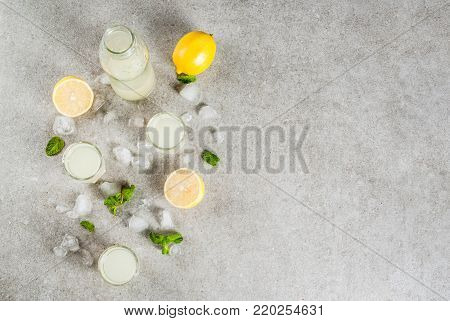Traditional italian alcoholic homemade beverage, lemon liqueur limoncello with fresh citrus, ice and mint, on grey stone table, copy space top view