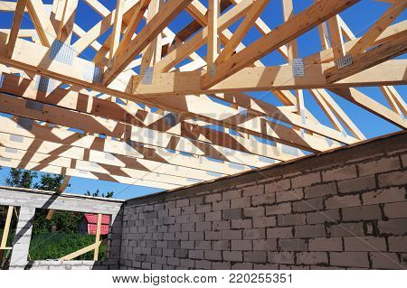 House roofing construction with wooden trusses. Timber roof trusses building. Wooden Roof Frame House Construction.