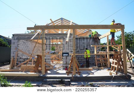 Roofers Building Wood Trusses Roof Frame House Construction. Roofing construction with wooden beams frame and terrace roof truss.