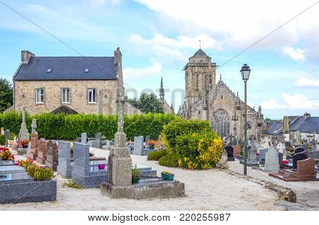 Locronan, France - August 10, 2017: View of the apse of the St Ronan church with the cemetery in the foreground