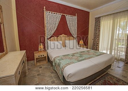 Double bed in suite of a luxury hotel room with curtains