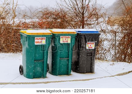 Green containers for garbage, a container for collecting plastic, covered with white fluffy snow. The first snow in the fall. garbage container snow winter background