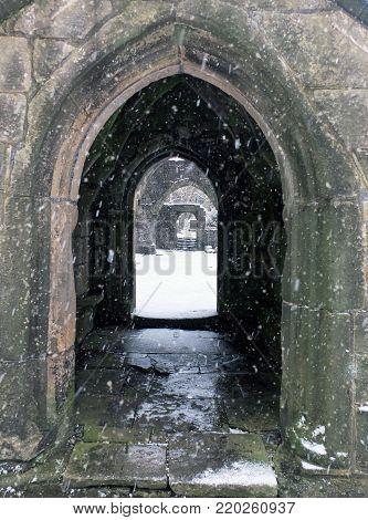 snow falling in the ruins of heptonstall church doorway