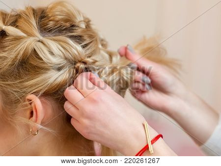 Beautiful blonde girl with a beautiful, neat hairstyle, close-up in a beauty salon. Professional hair care and creating hairstyles.