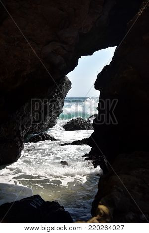 Seascape with waves and spray on rocky coast through a niche